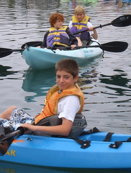 One boy in the foreground and two boys in the background kayaking at Pasadena summer camp
