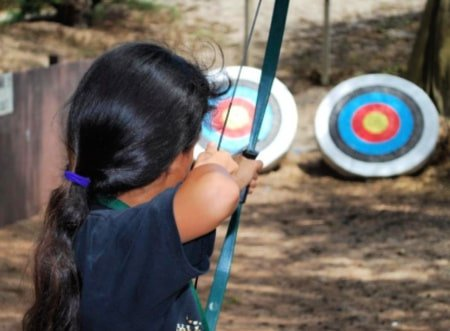 Female camper from Pasadena shooting an arrow from a bow at archery targets at summer camp. Hope she gets a bullseye in her archery activity!