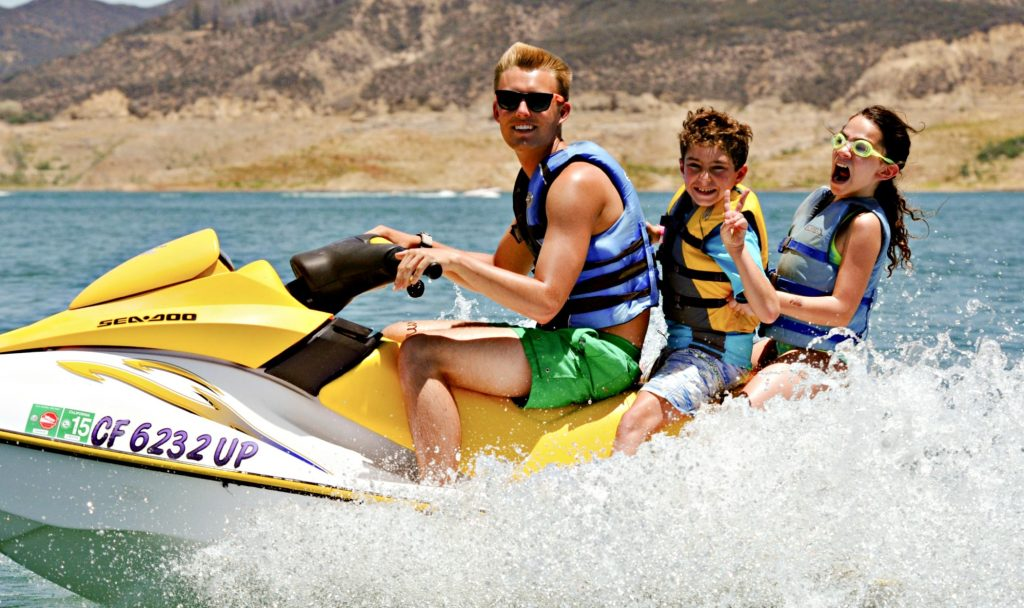 Two campers and their camp counselor from Pasadena jet skiing at camp.